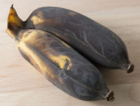 bad banana: Fruits, Black Ripen Wild Banana, Asian Banana or Cultivated Banana on A Wooden Cutting Board. Stock Photo