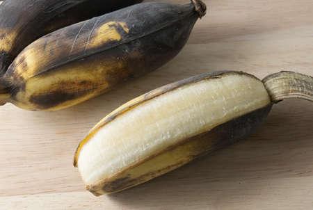 bad banana: Fruits, A Black Ripen Wild Banana, Asian Banana or Cultivated Banana on A Wooden Table.