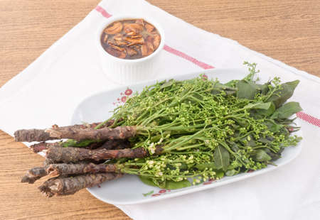 quinine: Thai Cuisine and Food, Dish of Fresh Margosa or Neem Leaves and Blossom Served with Sweet Sauce. Stock Photo