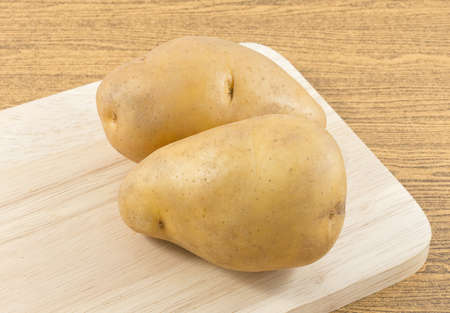 russet potato: Vegetable, Fresh Organic Potatoes on A Wooden Cutting Board.