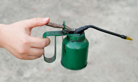 oiler: Hand Holding Old Dirty Oiler or Oil Can Coated in Grease and Dust, for Lubricating Machines.