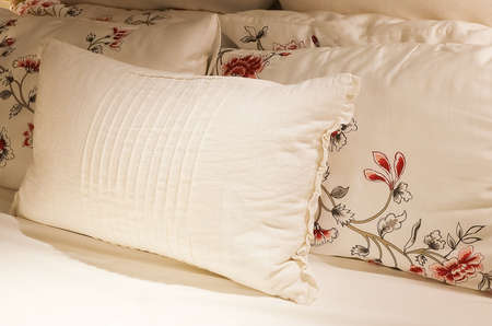 bedder: Luxury White Cozy Bed with Comfortable Soft Vintage Pillows in The Evening Time. Stock Photo
