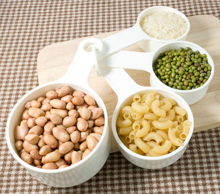 Foods High in Carbohydrate, Raw Pasta, Rice, Peanuts and Mung Beans in Plastic Measuring Spoons.