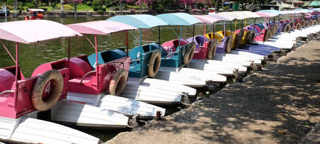paddle wheel: Row of Colorful Water Cycle Boats or Pedal Boats at The Dock in A Park. Stock Photo