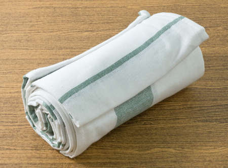 servilleta de papel: Kitchen Utensil, White and Green Napkin, Serviette or Kitchen Towel on Wooden Table with Copy Space for Text Decorated.