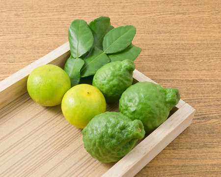 vegetable tray: Vegetable and Herb, Kaffir Lime with Persian Lime and Kaffir Leaves for Seasoning in Cooking on A Wooden Tray.