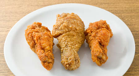 Cuisine and Food, A Plate of Small and Large Crispy Fried Chicken Wings Isolated on A White Background. Stock Photo