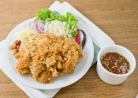 bagre: Thai Cuisine and Food, Thai Traditional Crispy Catfish Salad Served With Green Oak, Shredded Green Mango, Red Onion, Cabbage, Chili, Peanut and Spicy Sauce.