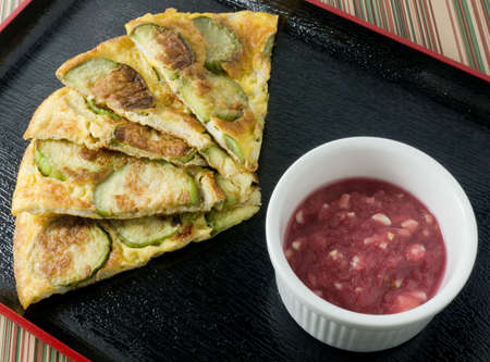 Thai Cuisine and Food, Thai Green Eggplant Omelet Served with Spicy Shrimp Paste Dip on A Black Tray.