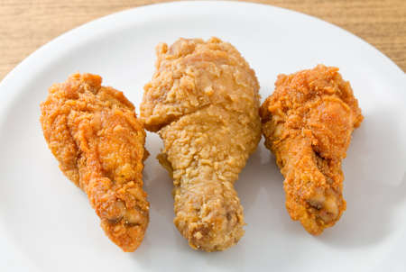 Cuisine and Food, Plate of Small and Large Crispy Fried Chicken Wings on Wooden Table. Stock Photo