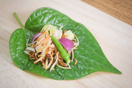 Thai Traditional Snack and Dessert, Dish of Miang Kum or Sweet and Spicy Betel Leaf Wrap Filled with Coconut, Peanuts, Dried Shrimp, Chiles and Lime. Stock Photo