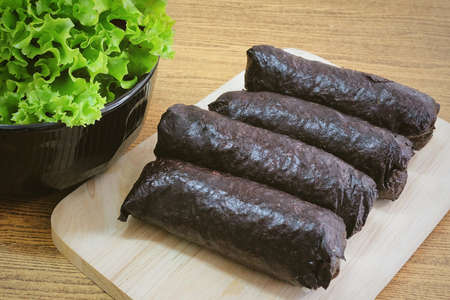 Japanese Cuisine, Traditional Unsliced Japanese Rice Maki Sushi Roll with Nori Seaweed on Cutting Board Served with Green Oak.