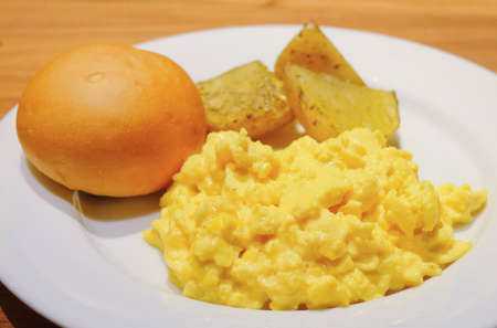 scrambled: Cuisine and Food, Plate of Delicious Scrambled Eggs with Round Bread and Grilled Potatoes on A Wooden Table.