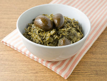 Chinese Traditional Food, Delicious Chopped Pickled Green Cabbage with Chinese Olives in A Bowl. Stock Photo