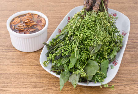 Thai Cuisine and Food, Close Up of Boil Margosa or Neem Leaves and Blossom Served with Sweet Sauce.