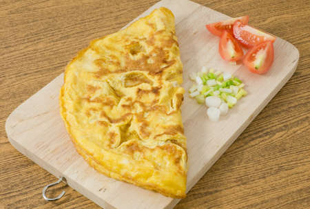 Thai Cuisine and Food, Thai Style Omelet with Tomatoes and Chopped Scallion on A Wooden Board.