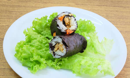 Japanese Cuisine, Traditional Vagetarian Japanese Rice Maki Sushi Roll Stuff with Tofu and Carrot Wrapped in Nori Seaweed Served on Green Oak.
