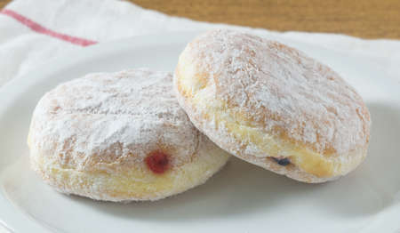 Food and Bakery, Two Glazed Sweet Donuts Strawberry Jam and Blueberry Jam with Icing Toppings. Banque d'images