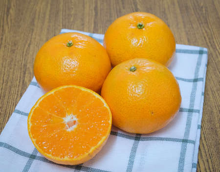 Fresh Ripe Whole and Cross Section Oranges on A Wooden Table, Orange Is The Fruit of The Citrus Species. Stock Photo