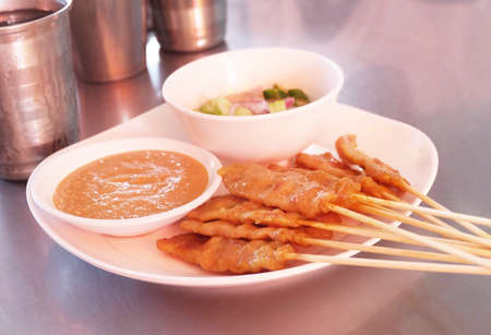 Food and Cuisine, A Plate of Grilled Pork Satay on Bamboo Skewer Served with Sweet Soy Sauce and Cucumber Salad. Stock Photo