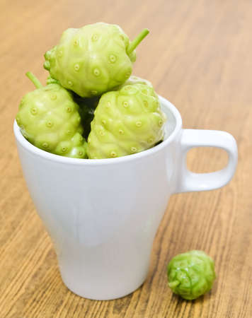 Vegetable and Herb, Noni, Morinda Citrifolia, Great Morinda, Indian Mulberry, Beach Mulberry or Cheese Fruits in A Cup with Polysaccharide, Vitamin A, C and Calcium. The Essential Nutrient for Life. Фото со стока - 129828123
