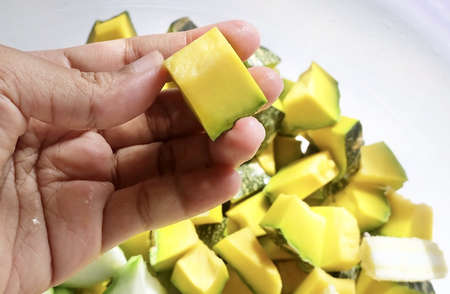 Hand Holding Raw Chopped Angled Gourds or Sponge Gourds with Pumpkins and Baby Corns Preparing for Cooking.