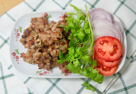 Thai Traditional Deep Fried Marinated Minced Pork Served with Coriander and Tomatoes on White Dish. 免版税图像