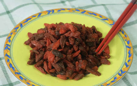 Berry Fruit, Goji Berries, Wolfberries or Lycium Barbarum Fruits in Yellow Dish with Chopsticks. A Good Source of Vitamin C, A, Zinc, Iron and Antioxidants. Stock Photo