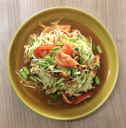 Thai Cuisine and Food, Top View of Thai Traditional Som Tam or Green Papaya Salad Made With Raw Papaya, Pickled Mussels, Tomato, Yardlong Bean, Chili, Peanut and Lime. 免版税图像