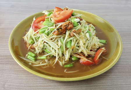 Thai Cuisine and Food, Thai Traditional Som Tam or Green Papaya Salad Made With Raw Papaya, Pickled Mussels, Tomato, Yardlong Bean, Chili, Peanut and Lime.