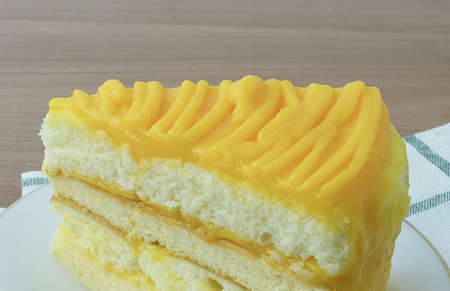 Snack and Dessert, A Piece of Mango Cake Made With Butter, Eggs, Sugar, Flour, Baking Powder and Flavorings Topped with Mango Sauce. 免版税图像