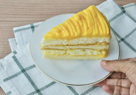 Snack and Dessert, Hand Holding A Piece of Mango Cake Made With Butter, Eggs, Sugar, Flour, Baking Powder and Flavorings Topped with Mango Sauce.