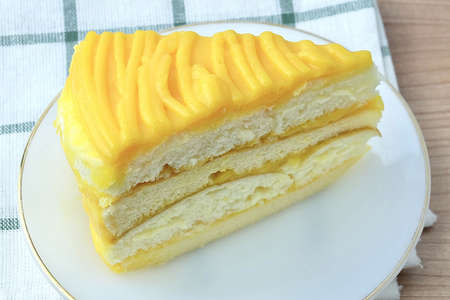 Snack and Dessert, A Piece of Mango Cake Made With Butter, Eggs, Sugar, Flour, Baking Powder and Flavorings Topped with Mango Sauce. Stock Photo