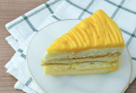 Snack and Dessert, A Piece of Mango Cake Made With Butter, Eggs, Sugar, Flour, Baking Powder and Flavorings Topped with Mango Sauce.