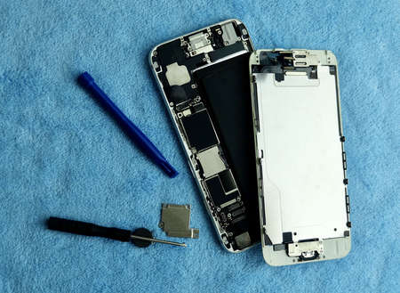 Close Up Of Broken Smartphone with Screwdriver, Tweezers and Repair Equipments on The Table. 免版税图像