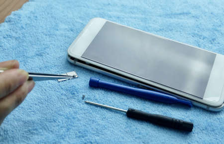 Close Up Of Technician Repairing Smartphone with Tweezers on The Table.