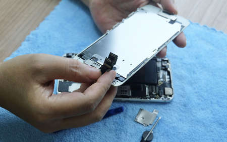 Close Up Of Technician Opening and Repairing Smartphone with Screwdriver on The Table.