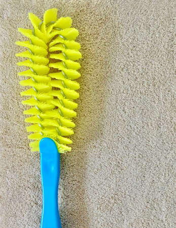Close Up Yellow Plastic Cleaning Brush with Blue Handle Laying on Brown Towel, Used Wet with Wwater or Ccleaning Fluids.