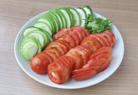 Vegetable, Top View of Fresh Sliced Ripe Tomatoes, Cucumbers with Corianders on A White Plate. Stock Photo