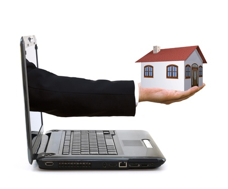 exiting: hand with a house exiting from a laptop Stock Photo