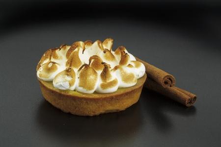 pie de limon: pastel de merengue en un fondo negro