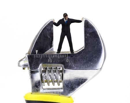 crushing: wrench crushing a tiny man closeup