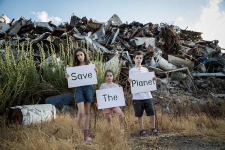 惑星を保存します。子供の巨大なゴミ捨て場に立っている標識を保持 写真素材 - 87943639
