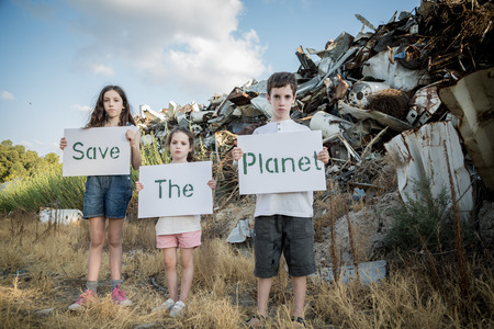 Save the planet. young kids holding signs standing in a huge junkyard Standard-Bild