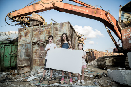 Save the planet. young kids holding signs standing in a huge junkyard Reklamní fotografie