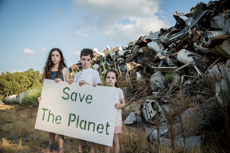 Save the planet. young kids holding signs standing in a huge junkyard 写真素材