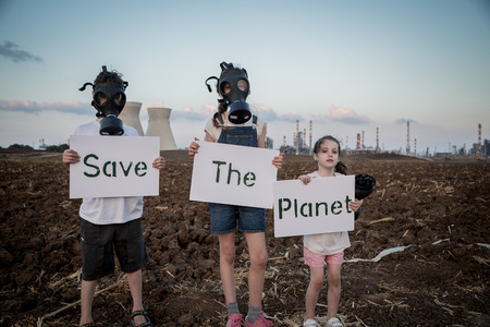Save the plant. Young kids holding signs standing near a refinery with gas masks Reklamní fotografie