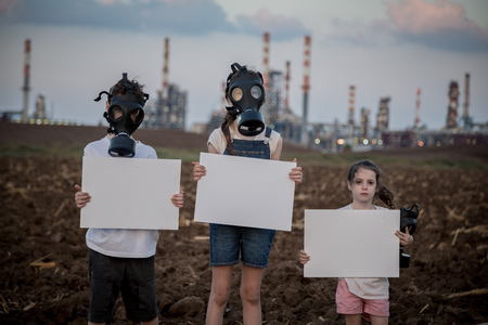 Save the plant. Young kids holding signs standing near a refinery with gas masks Standard-Bild