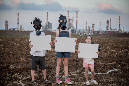 Save the plant. Young kids holding signs standing near a refinery with gas masks 写真素材