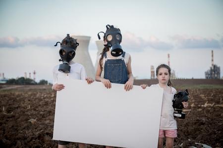 プラントを保存します。ガスマスクを装備した製油所の近くに看板を持つ若い子供たち 写真素材 - 87789401